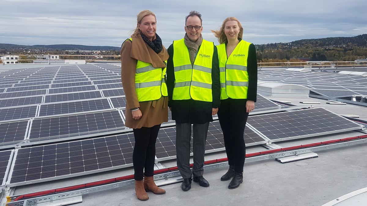 To damer og en mann står på et tak med solceller. Foto