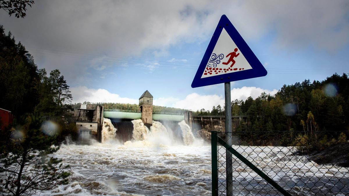 Høy vannstand foran en kraftstasjon og advarsel på skilt. Foto