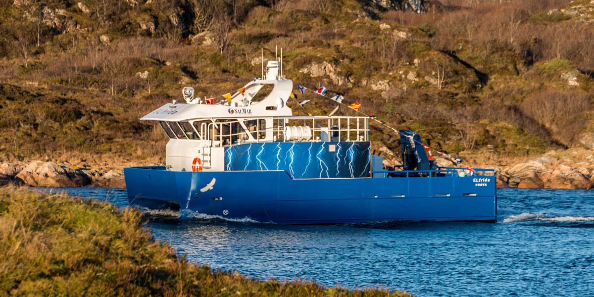 Fiskebåt kjører langs land. Foto