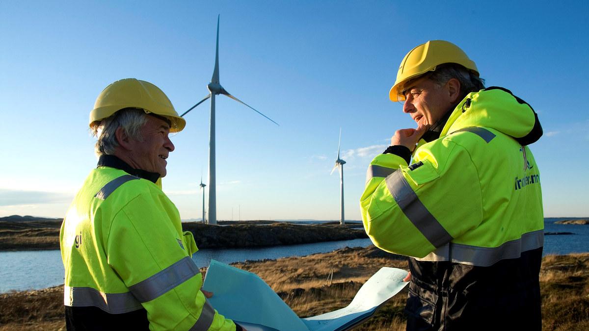 To menn i vernedress og hjelm snakker sammen foran en vindmølle. Foto