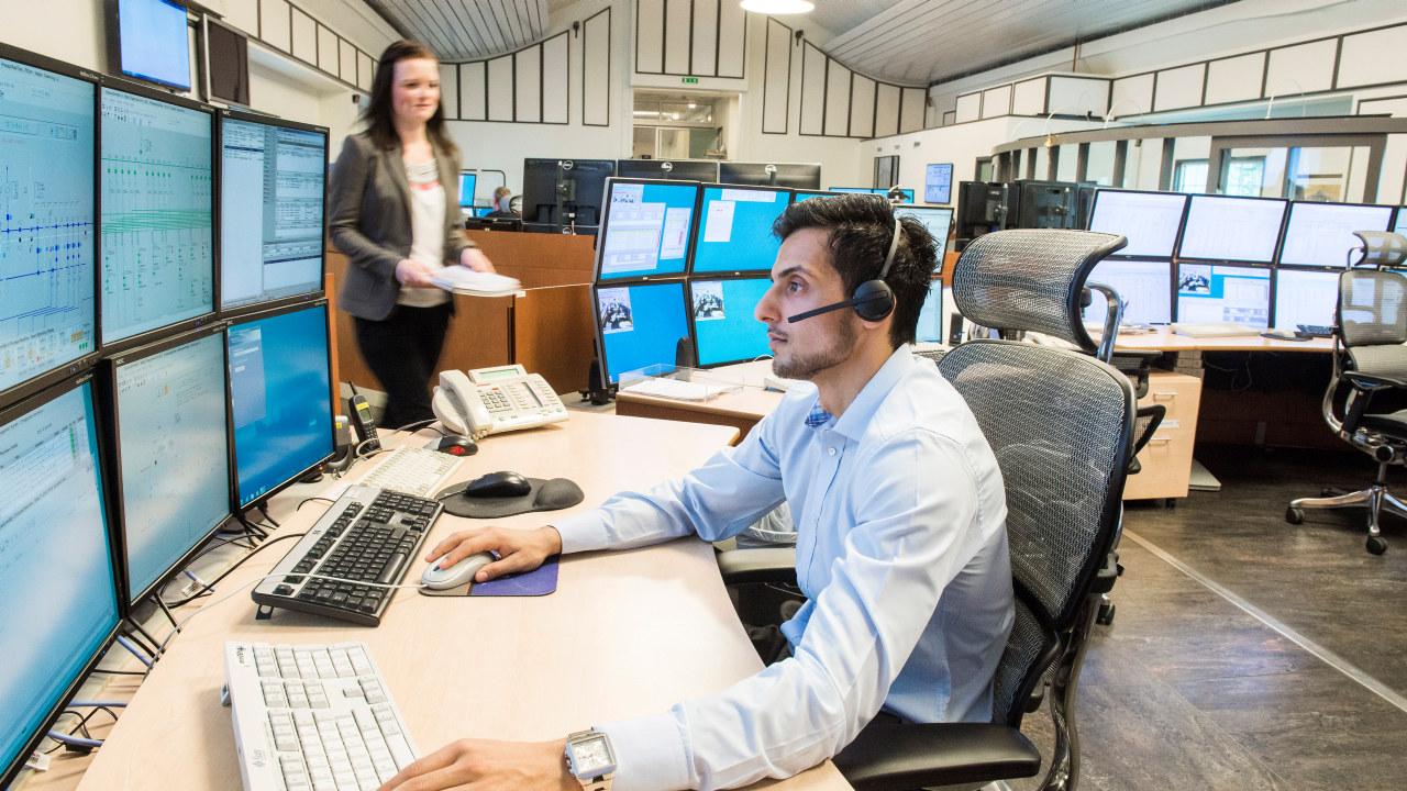 Bilde av en dame som kommer inn i et rom med mange skjermer og en  mann ved et skrivebord. Foto