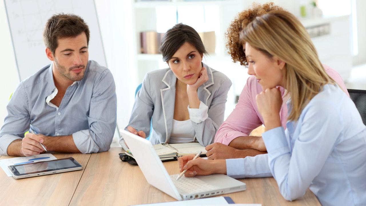 Fire mennesker sitter ved et møtebord med PC, nettbrett og papirer. Foto
