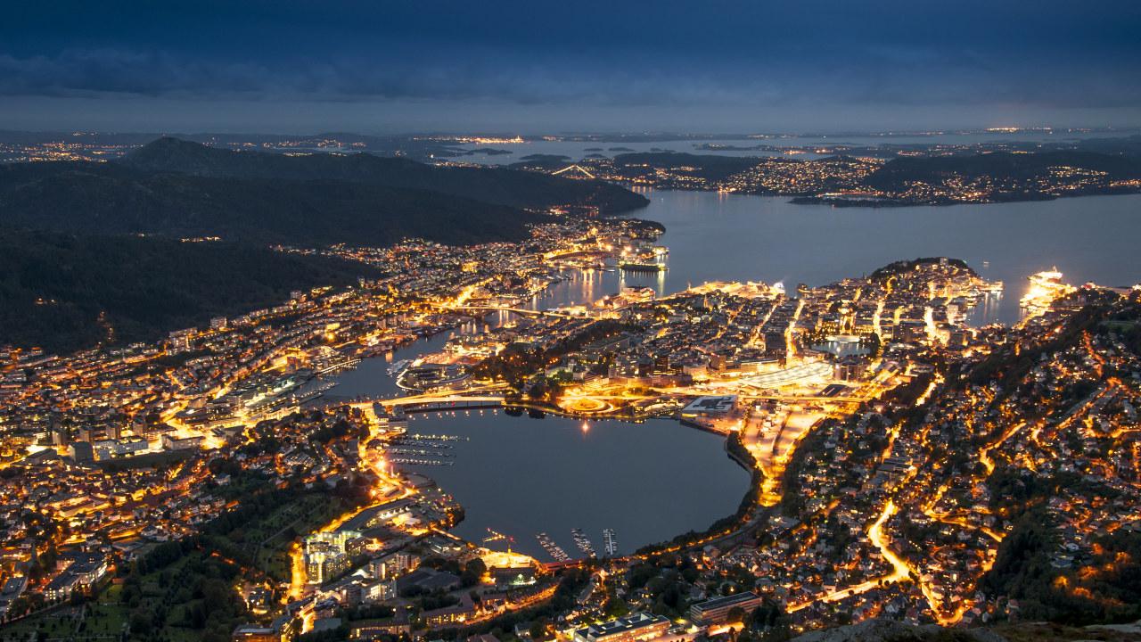 By ved vann og omkranset av fjell om kvelden. Foto