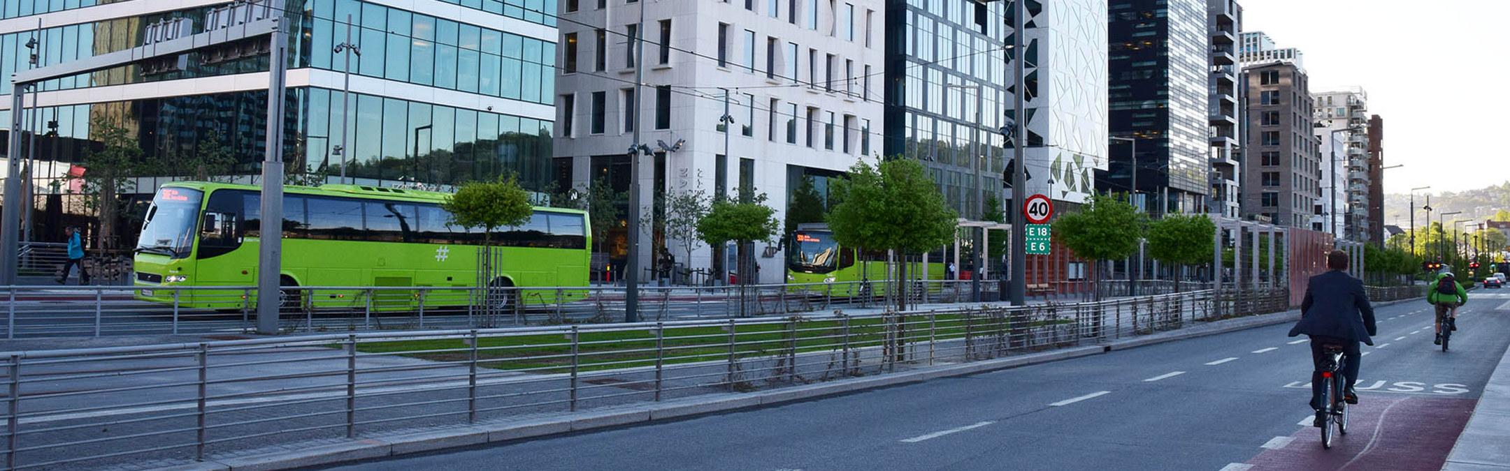 Buss og sykkelist i gate med høye bygg. Foto