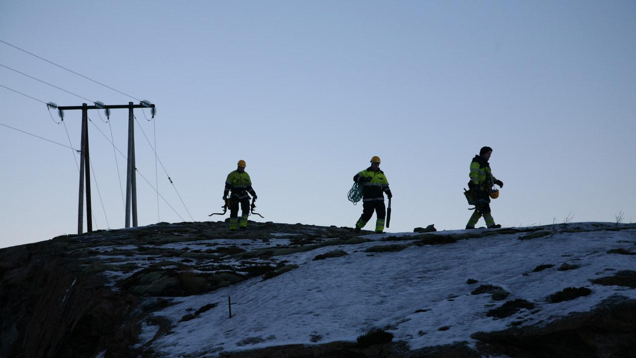 bilde av tre energimontører som går over fjellet og en strømmast