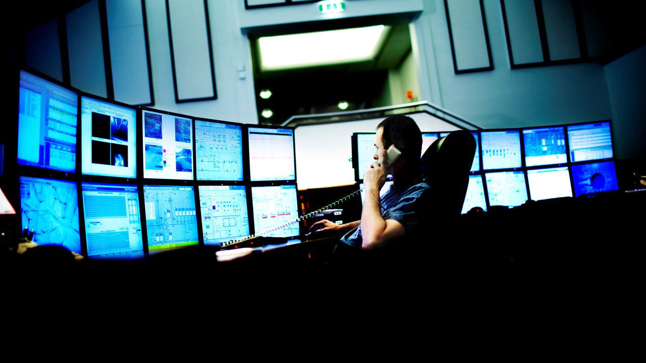 Driftssentralen med mange dataskjermer og mann i telefon. foto