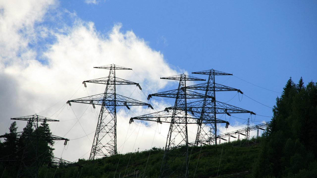 Kraftmaster på toppen av grønnkledd ås. Foto