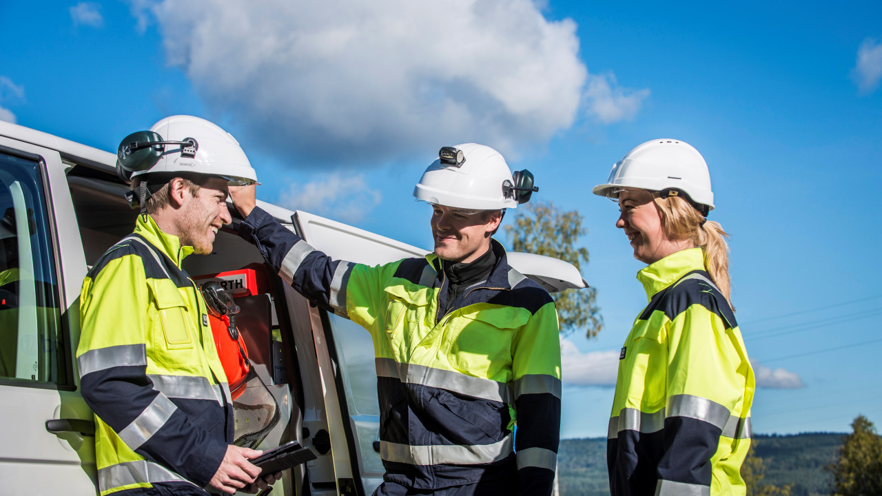 Tre energimontører med hjem og gul jakke og hjelm. foto