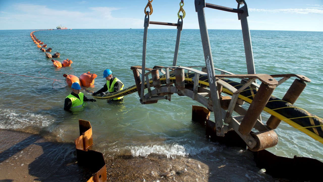 kabler i sjøen og to arbeidere i vannet. foto