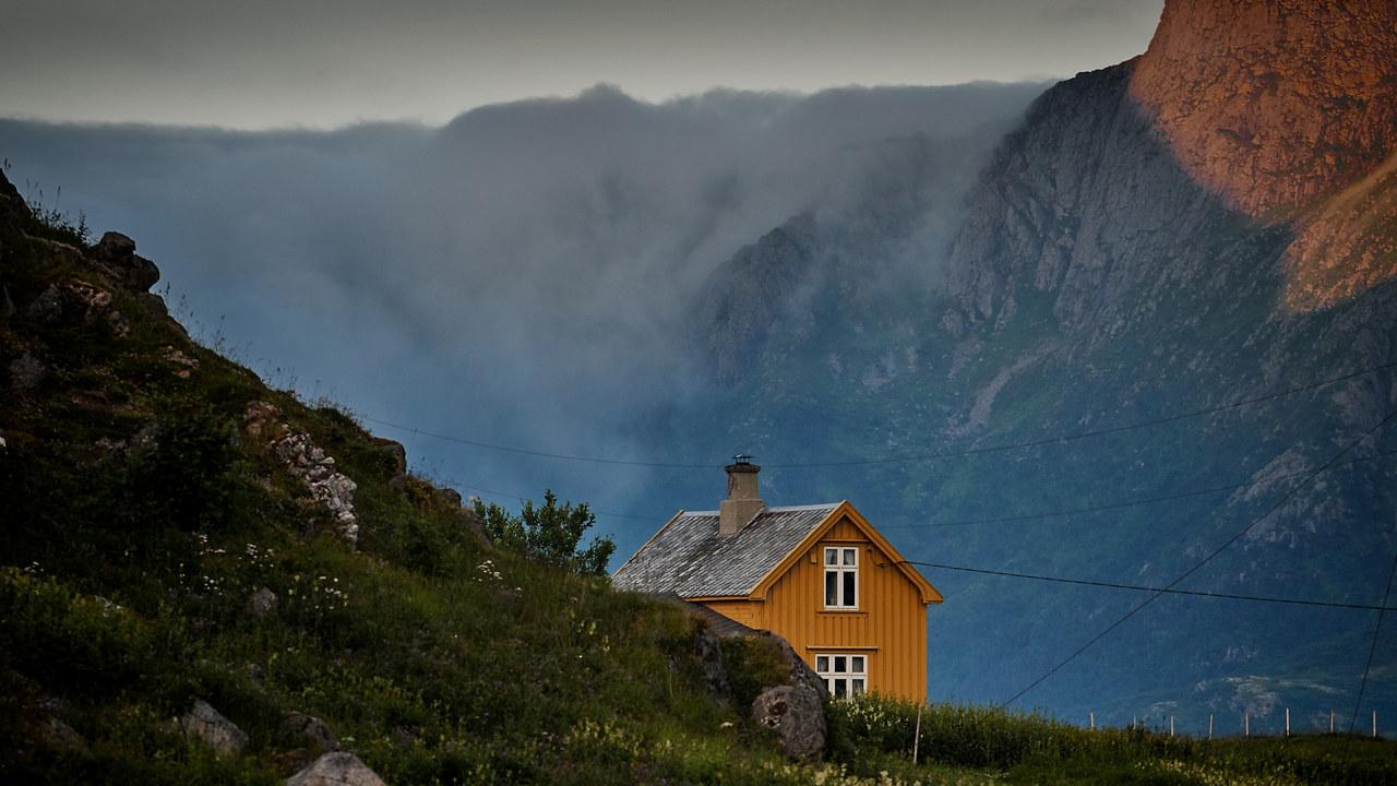 Gult hus i grønn natur og fjell. foto