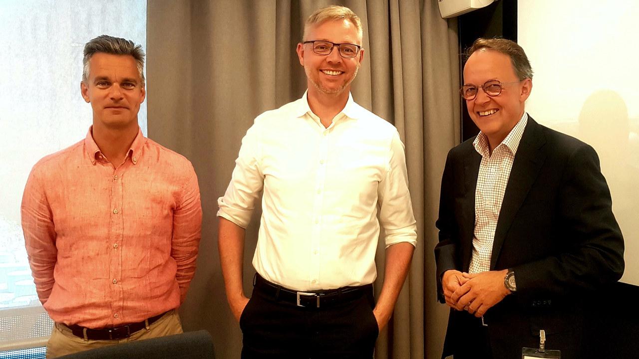 Tre menn i dress innendørs. foto