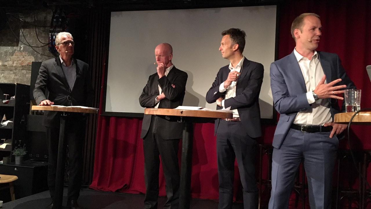 Fire menn på scene med rødt teppe bak. foto