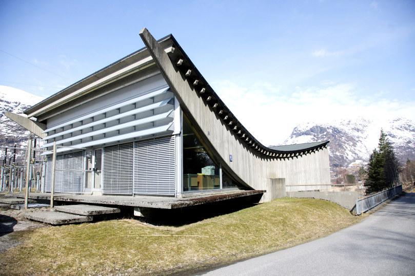 Bygning med bøyd tak med natur rundt. foto