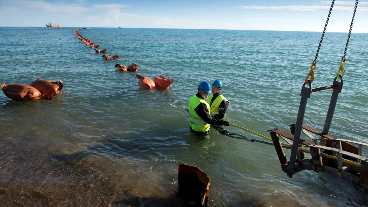 To menn i havet som jobber med en kabel. foto