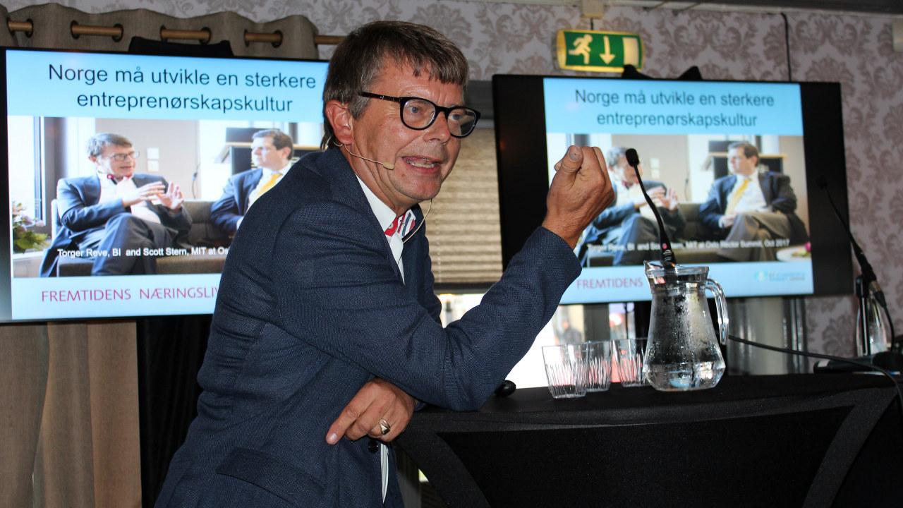 Mann som snakker på en scene. foto