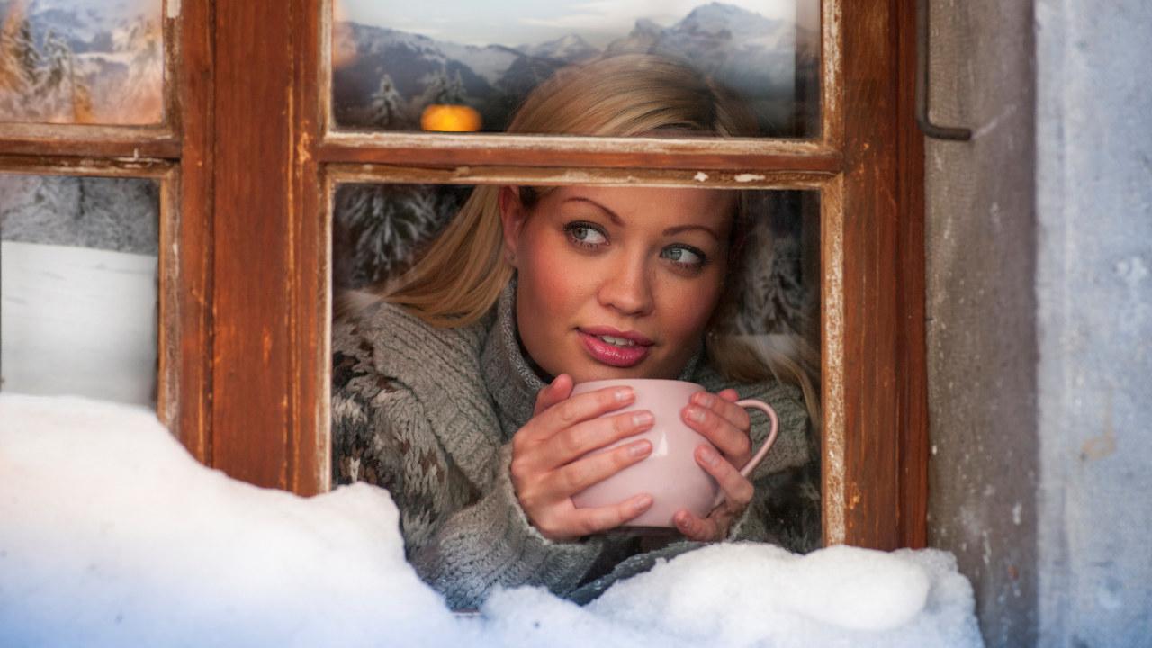 Dame med kaffekopp som ser ut av vindu. foto