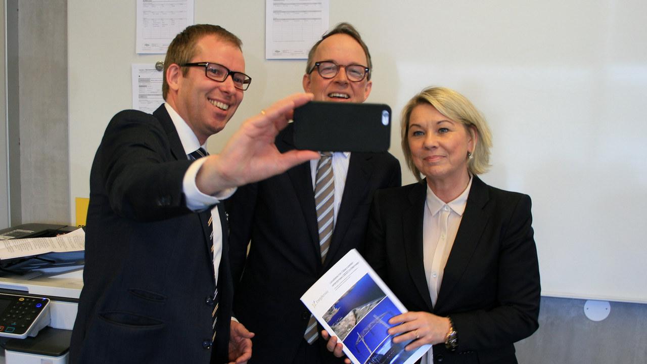 Tre personer som tar selfie med mobilen. Foto