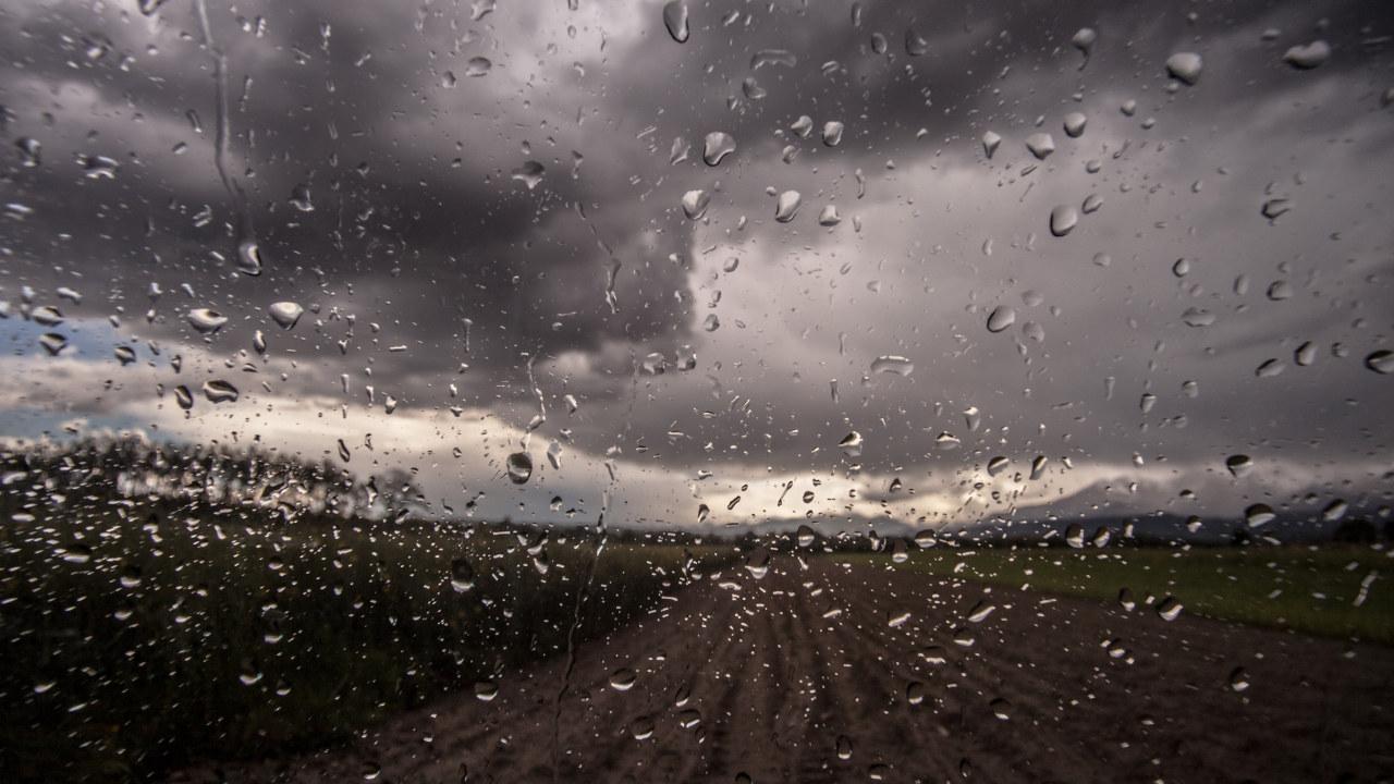 Bildet av regn som trommer ned på en åker og mørke skyer i horisonten.Foto