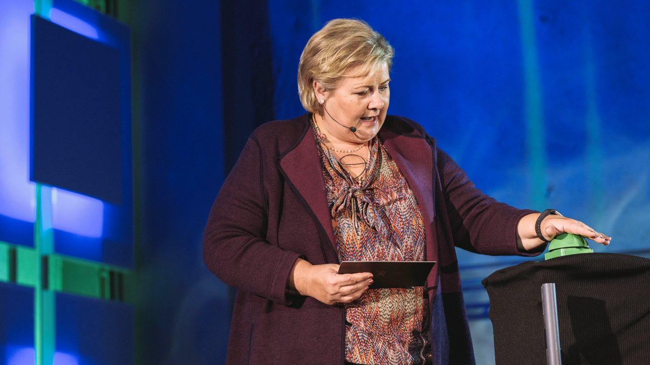 Statsminister Erna Solberg trykker på en grønn knapp. foto
