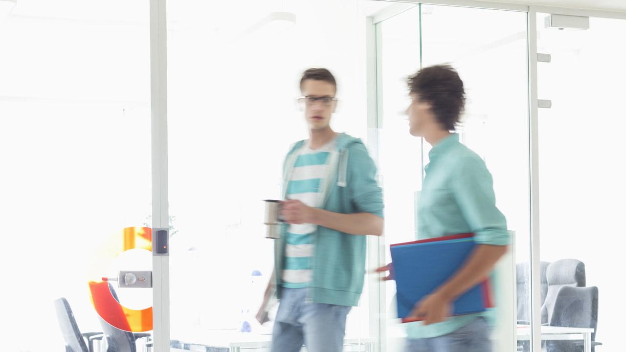to menn går forbi kontorplasser