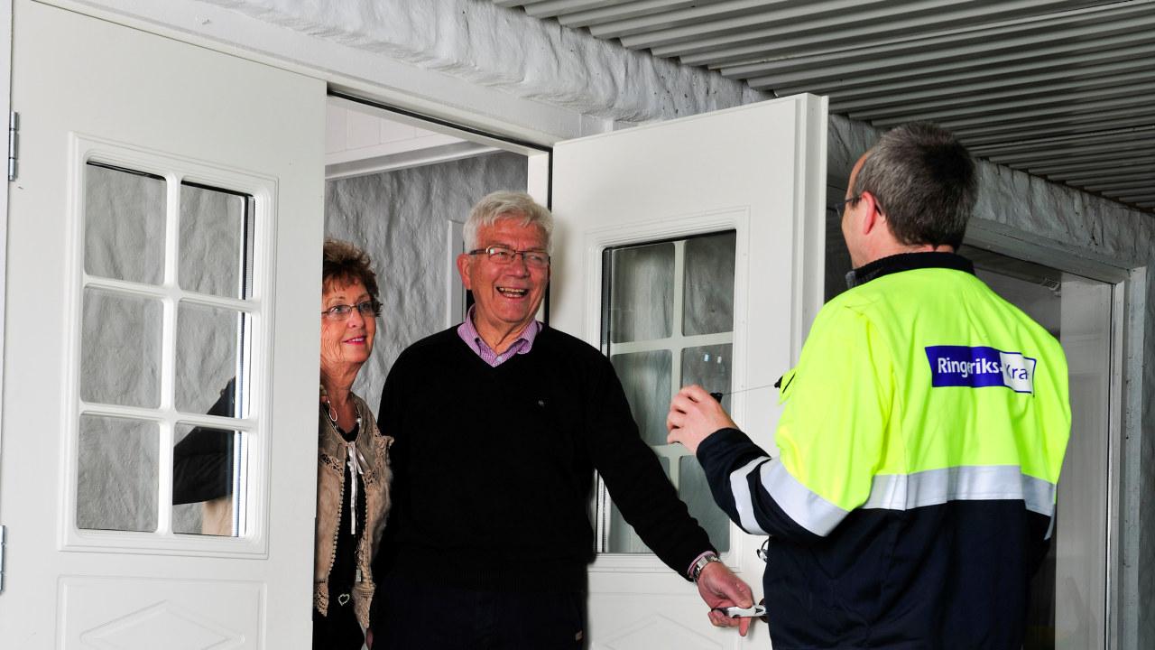 Mann i arbeidsdress fra Ringeriks-Kraft snakker med et par. Foto