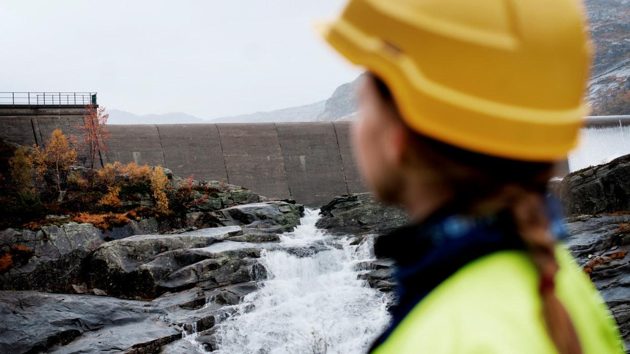 Dame står ved siden av et damkraftanlegg. Foto
