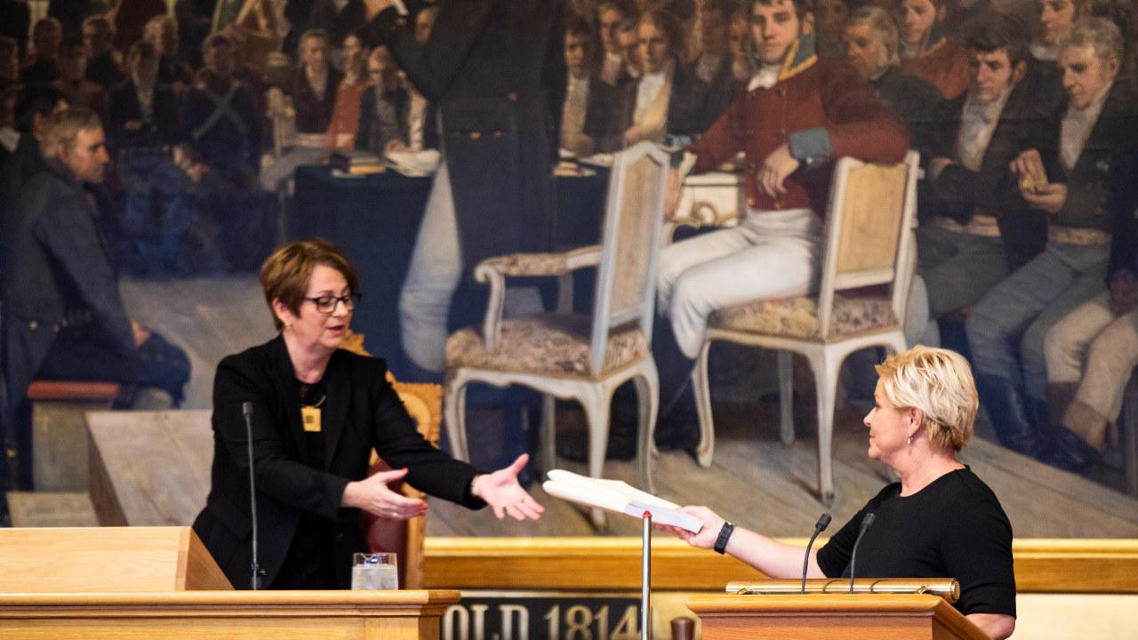 En dame tar i mot en dokumentbunke fra en annen dame. Foto