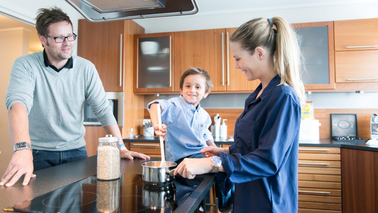 Foreldre og ett barn lager mat sammen på kjøkkenet. Foto