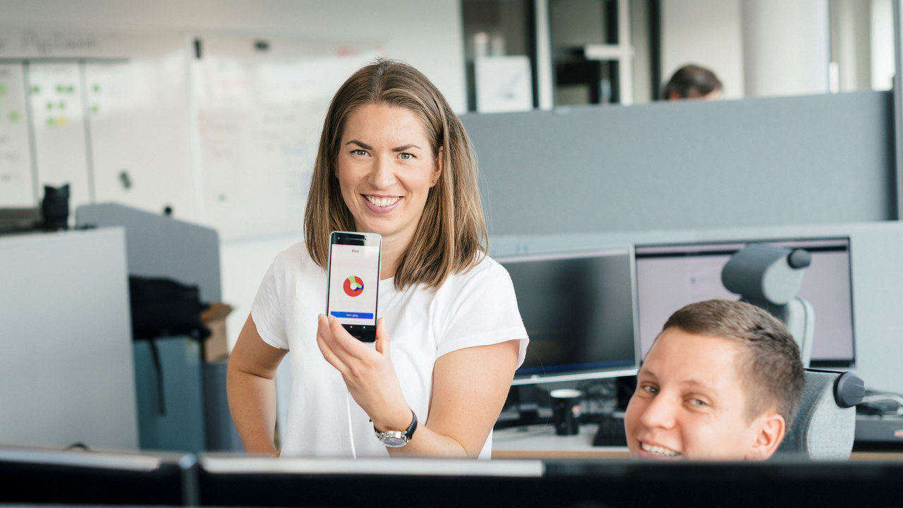Kvinne som holder opp en mobiltelefon. foto