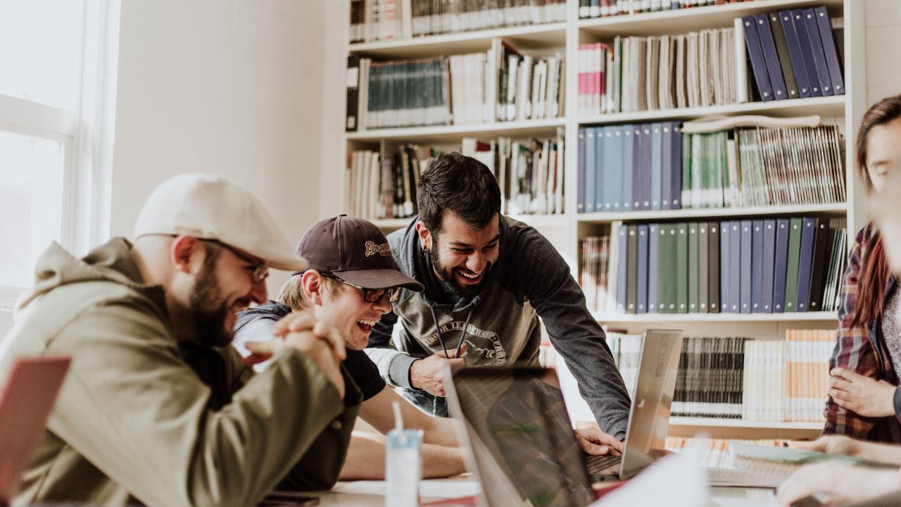 tre unge gutter henger over en PC og ler. Foto