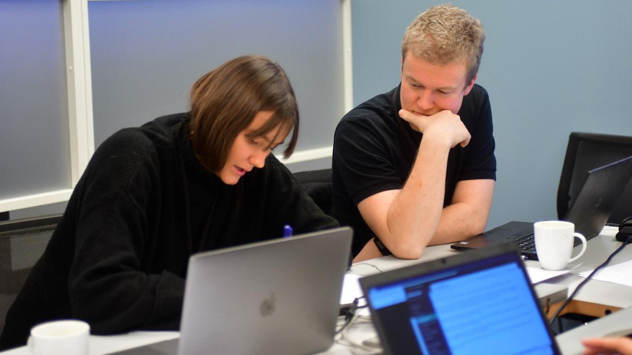 Mennesker som sitter med datamaskin. foto
