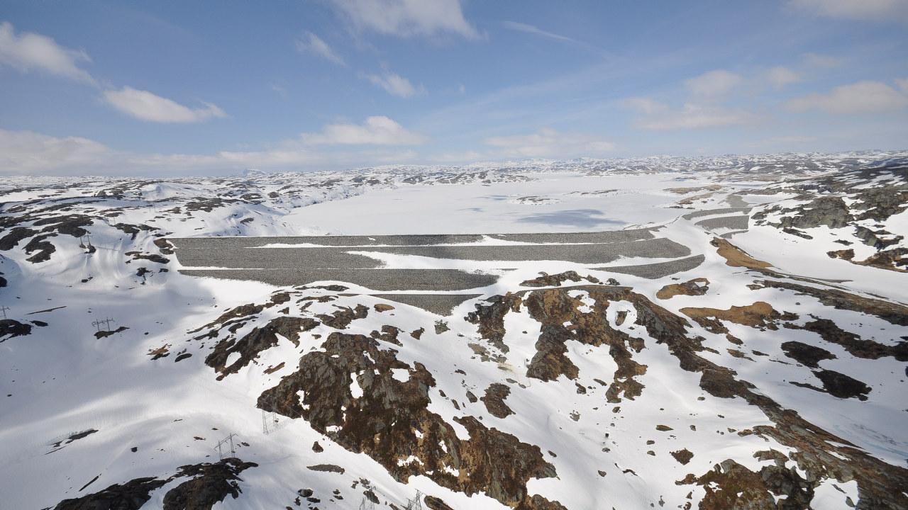 Bilde av en snødekt dam med fjell rundt