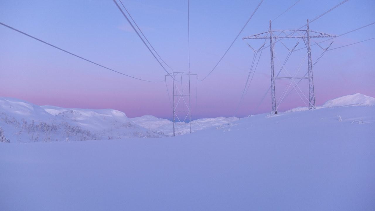 Store snømengder og strømmaster i solnedgang. Foto