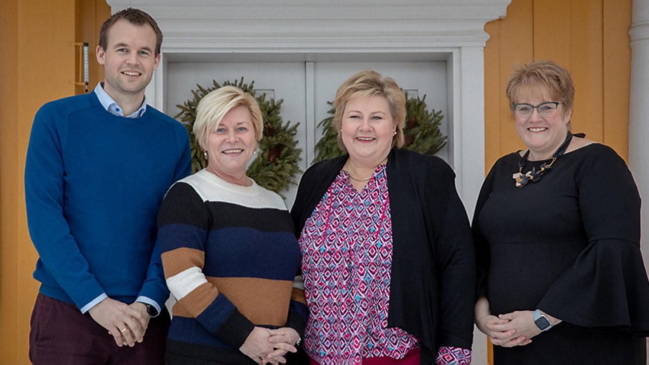tre kvinner og en mann som smiler til kamera. foto