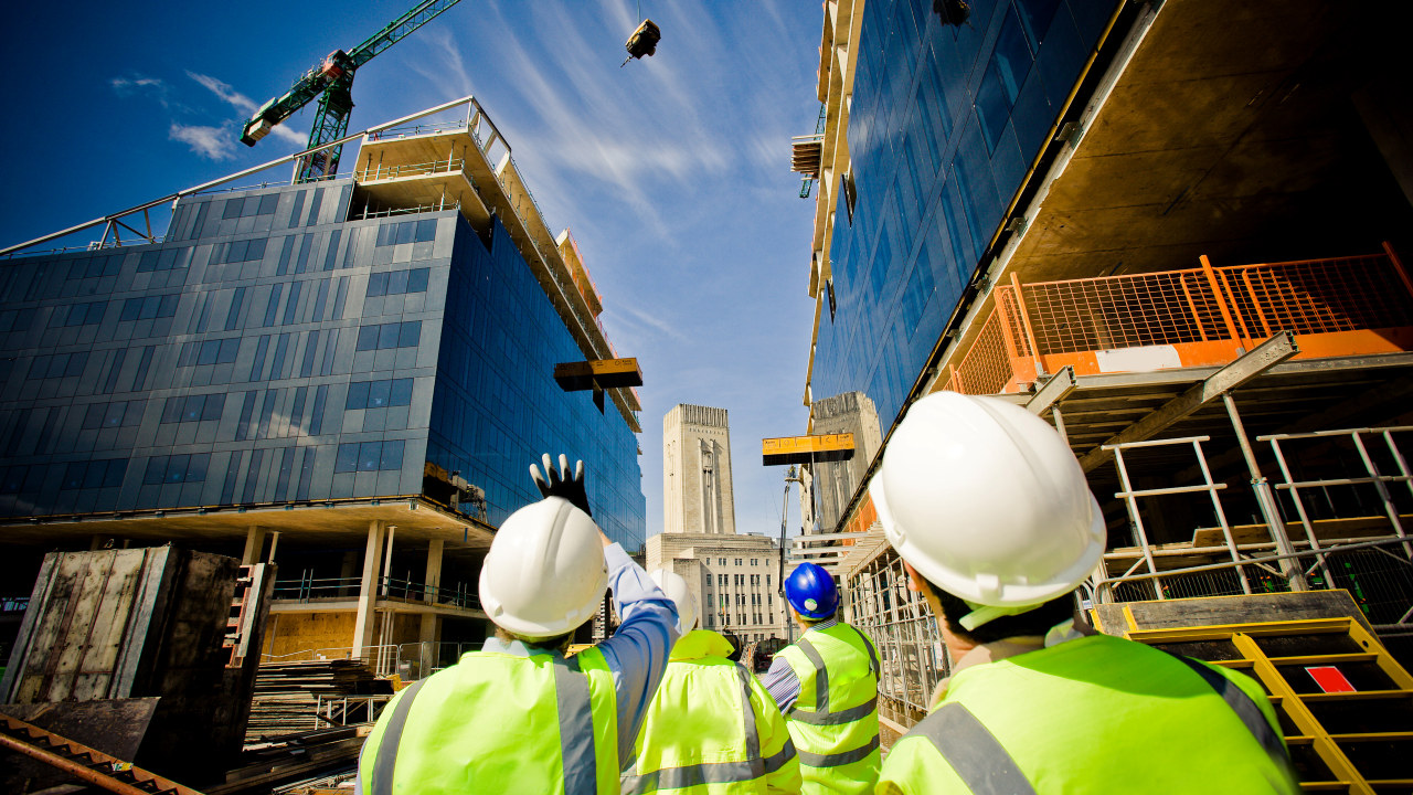 Anleggsarbeidere på en byggeplass titter opp på kranene