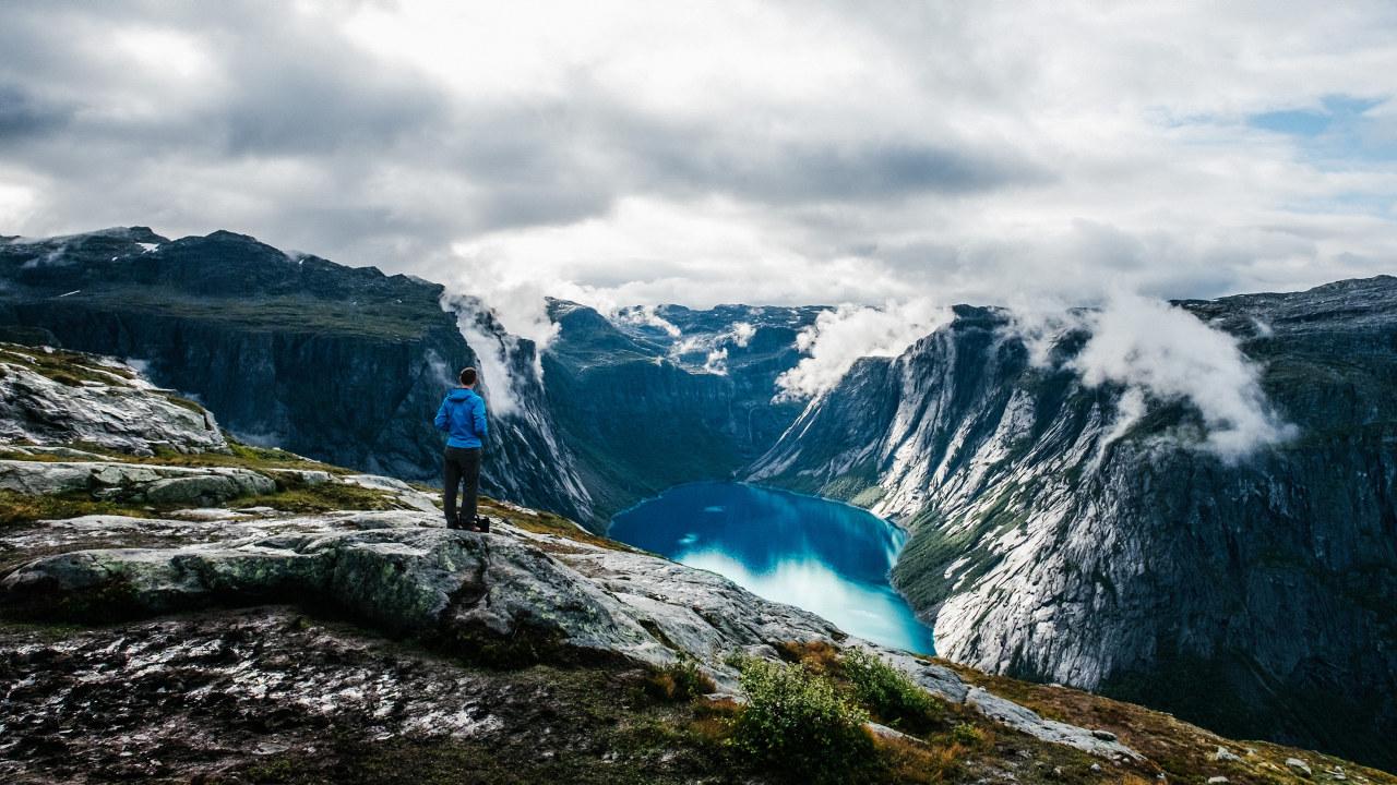Mann stor og ser ut over fjell og ned i et vann. Foto