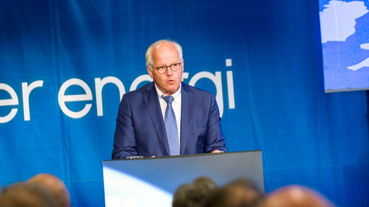 Mann i dress på scene med blå bakgrunn. foto