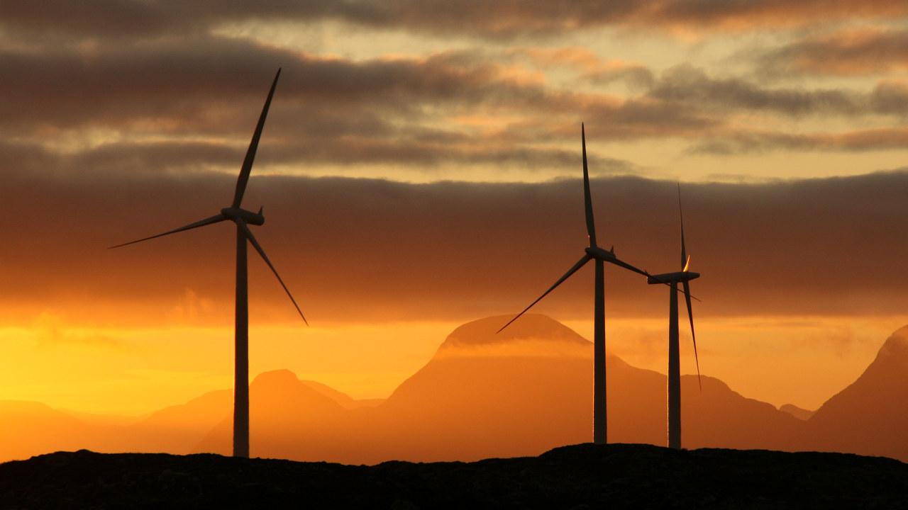 Vindmøller i solnedgang med fjell i bakgrunnen. Foto