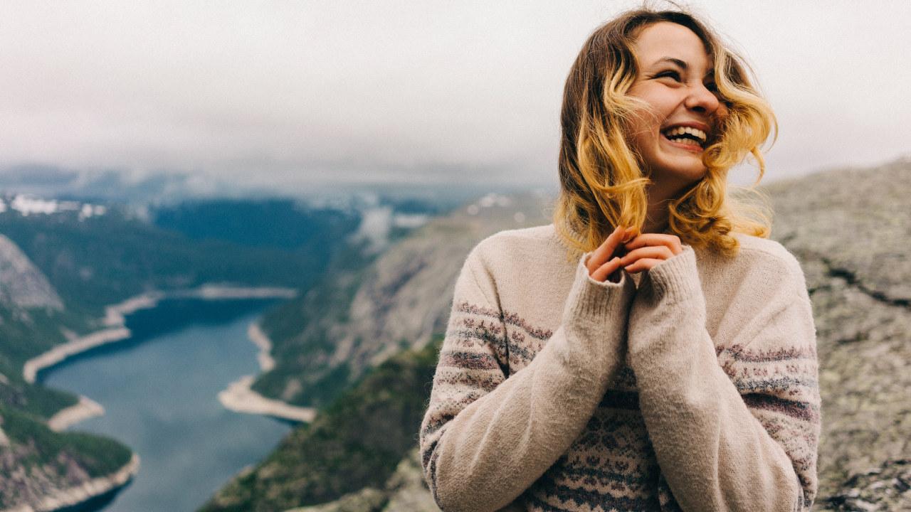 Ung dame står på Trolltunga fjelltopp og ler. Foto