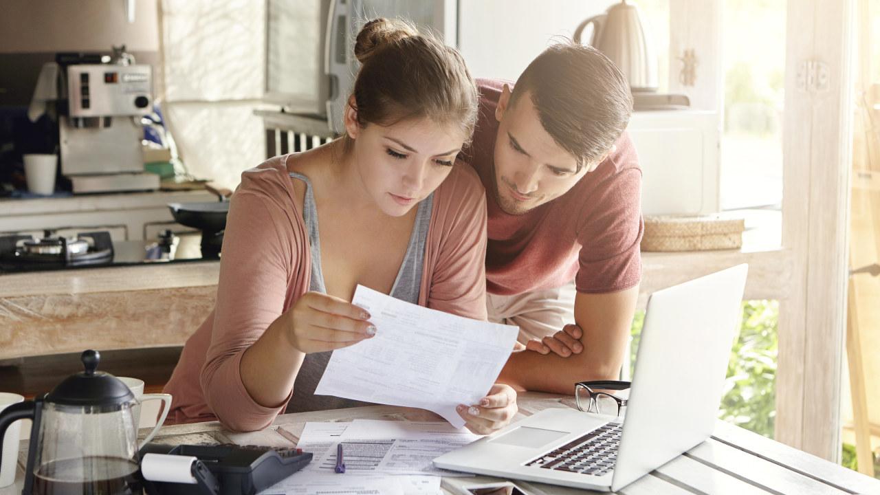 Ungt par gjør betaler regninger på en PC. Foto