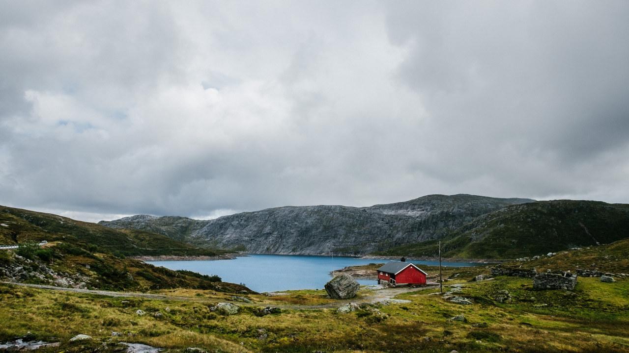 Et hus ligger ved et vann omkranset av lave fjell. Foto