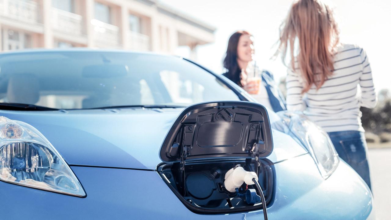 To unge damer står og snakker sammen mens en elbil lader. Foto