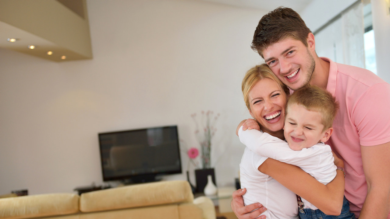 happy young family with kids in bright modern living room have fun and looking big flat lcd tv Forbruker