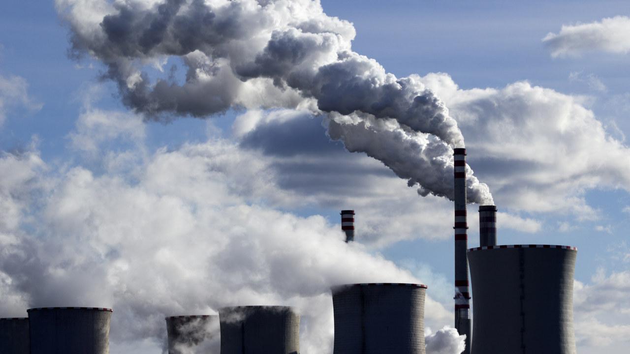 Foto. Hvit røyk velter ut av pipene på et kullkraftverk