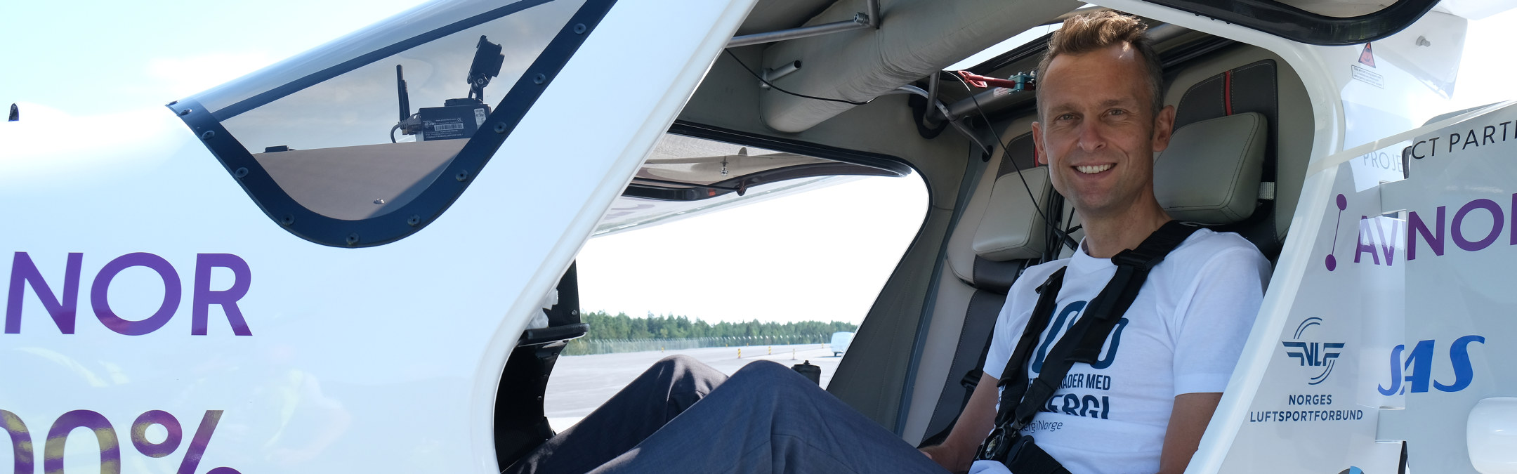 Foto: En mann sitter i et flysete og smiler.
