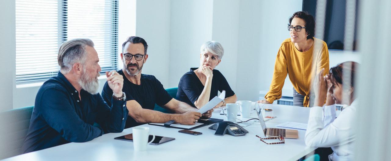 Fem mennesker rundt et møtebord snakker sammen. Foto
