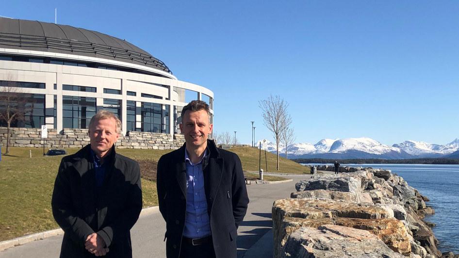 To menn står ved siden av hverandre med snøkledde fjell i bakgrunnen. Foto