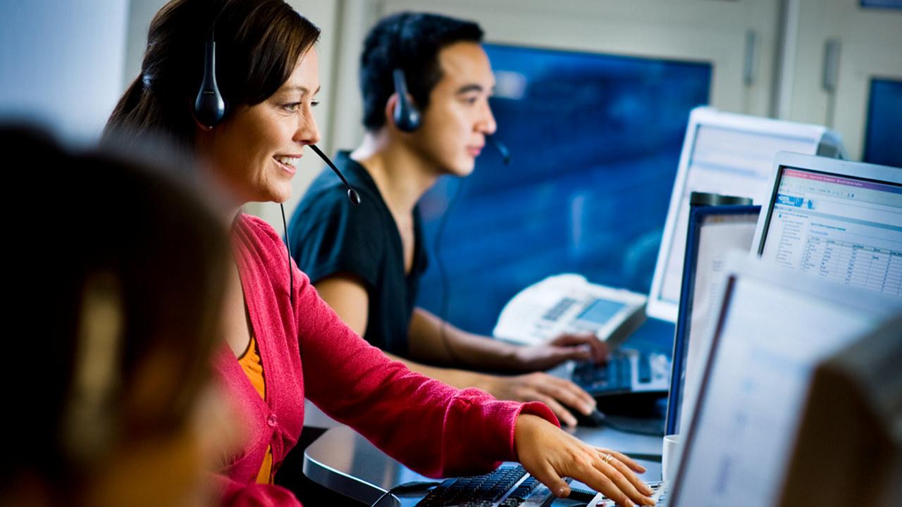 To kunderådgivere med headset foran PC-skjermer