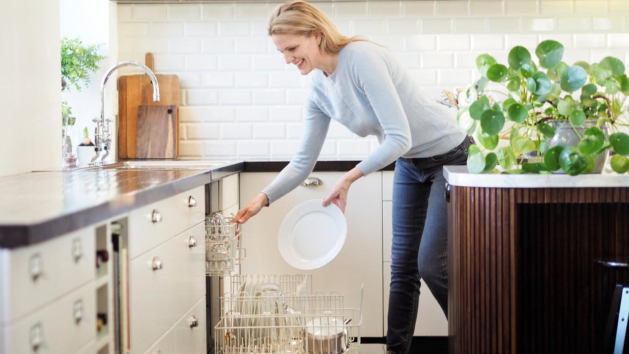 Dame smiler mens hun rydder ut av en oppvaskmaskin. Foto