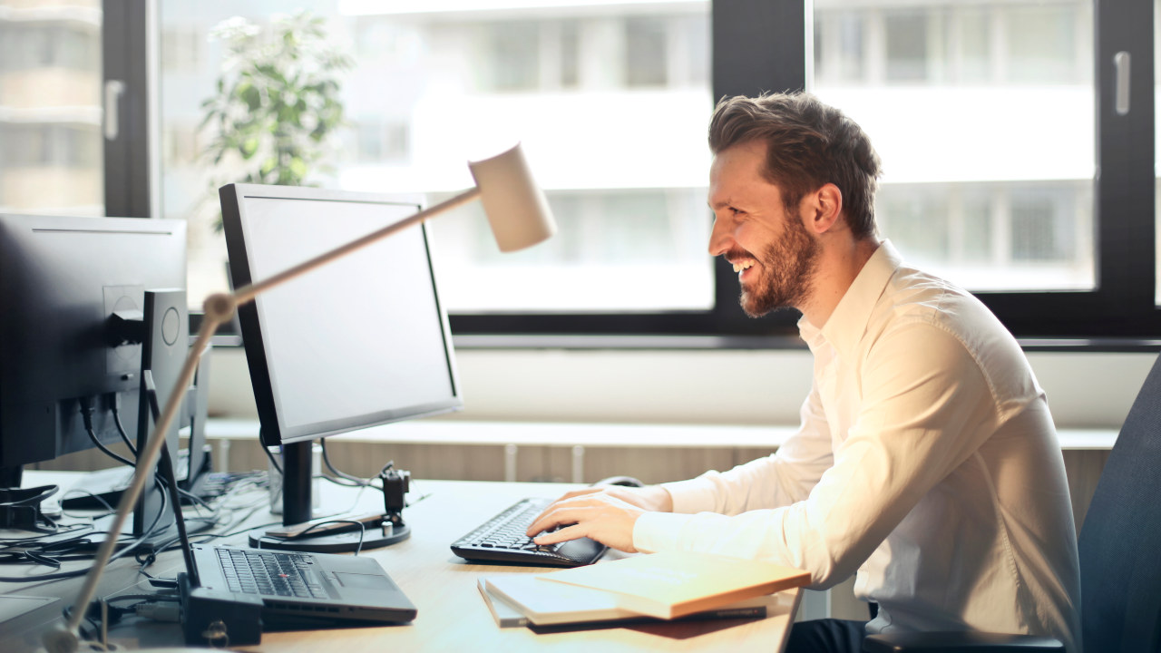 Mann sitter og smiler foran en PC på et kontor. Foto